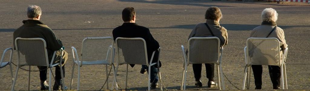 Menschen sitzen alleine auf Stühlen in einem Park